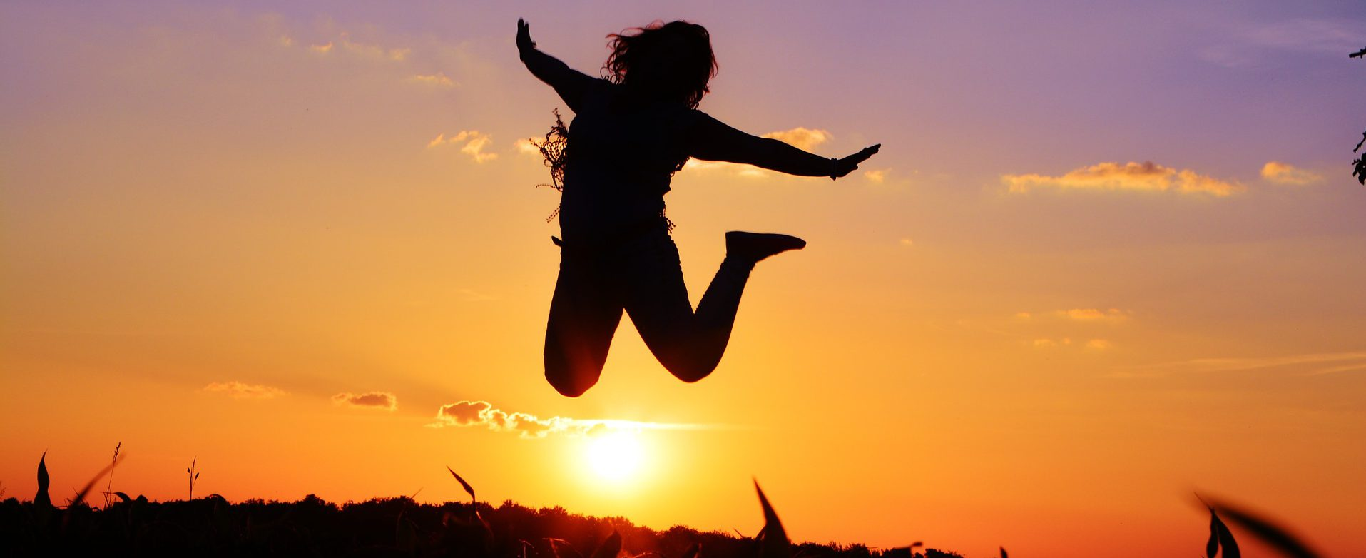 Person leaping in front of sun