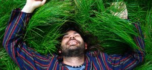 Happy man laying in grass