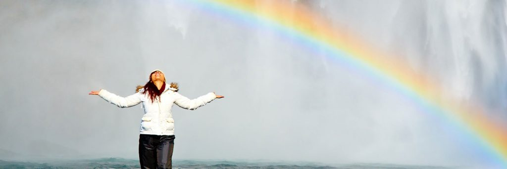Lady in front of rainbow