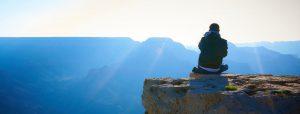 Man sitting on ledge meditating