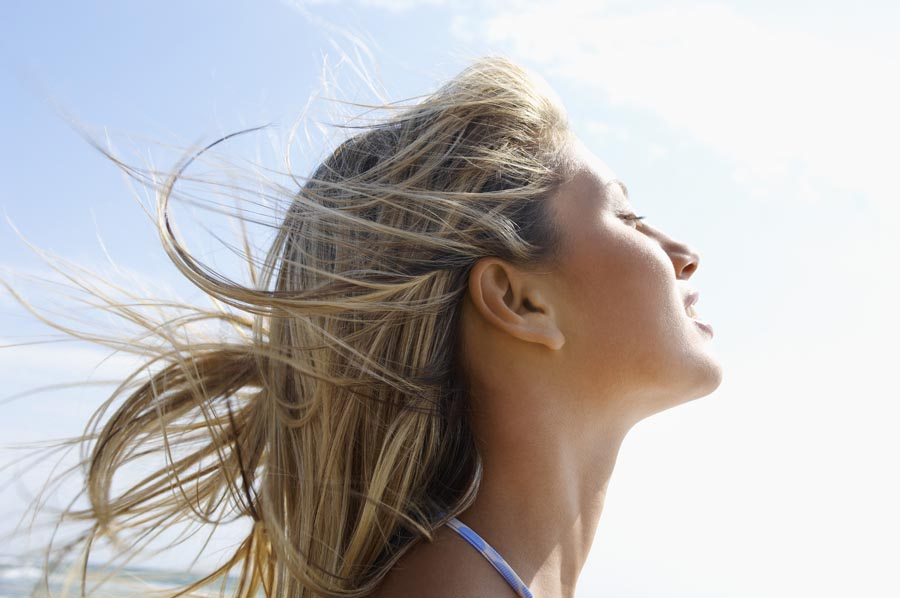 Young woman on beach with wind-swept hair, close up, side view, head shot