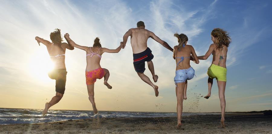 Man with four women running and jumping on beach, back view